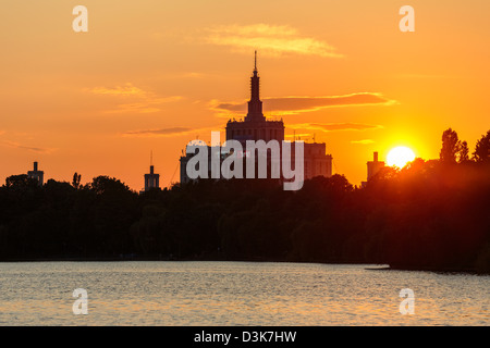 Sunset over House of the Free Press. View from the lake in Herastrau Park, Bucharest, Romania. - Stock Photo