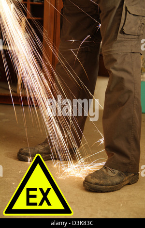 Feets of a worker with sparks of an angle grinder and a sign - Stock Photo