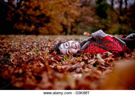 A woman lying on the ground hold an autumn leaf - Stock Photo