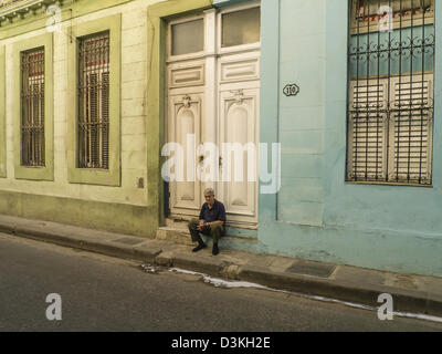 A lone older adult male sits on the stoop of his house along a street of colorful buildings early morning in Havana, - Stock Photo