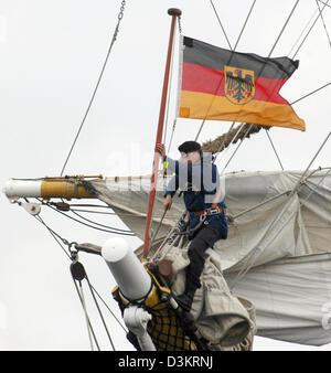 (dpa) - A marine hoists the German flag  and sails on the tall ship 'Gorch Fock' in Kiel, Germany, Thursday 25 August - Stock Photo
