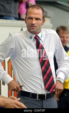 (dpa) - Holger Fach, coach of Wolfsburg, touches his trousers in front of the coach area dduring the Bundesliga - Stock Photo