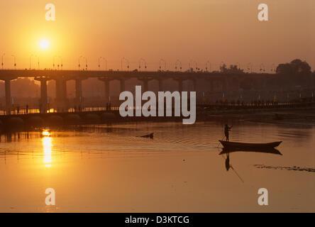 Boat being poled past the Grand Trunk Road bridge at sunset, Maha Kumbh Mela 2001, Allahabad, Uttar Pradesh, India