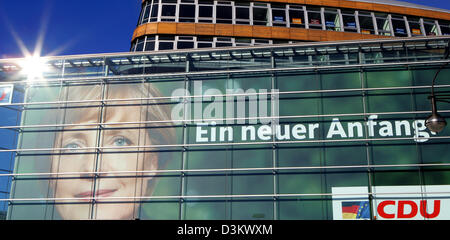 (dpa) - The sun rises and mirrors on the facade of the headquarter of the Christian Democratic Party (CDU) in Berlin, 18 September 2005. The poster attached to the facade features a portrait of Angela Merkel, chairwoman of the CDU and chancellor candidate. Supporters and journalists are going to follow the election results of the 2005 German Bundestag election at the  party headqua