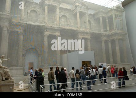 (dpa) - Visitors stand in the great exhibition hall in front of the ancient 'market gate of Milet', which is covered - Stock Photo