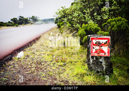 A warning sign on the road to Piton de la Fournaise volcano, French Reunion Island, Indian Ocean - Stock Photo