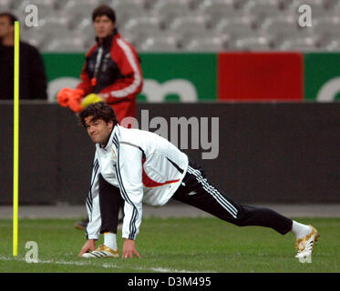 (dpa) - Germany's team captain Michael Ballack (front) conducts stretching exercises as assistamt coach Joachim - Stock Photo