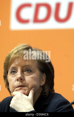 (dpa) - CDU Chairwoman and designated German Chancellor Angela Merkel sits at the podium during the CDU's small party convention in Berlin, Germany, 14 November 2005. Merkel defended the formation of a grand coalition. Photo: Tim Brakemeier