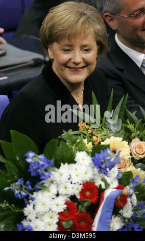 (dpa) - New elect German Chancellor Angela Merkel of the Conservatives (CDU) stands with a big bouquet in the plenary - Stock Photo