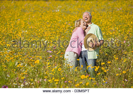 Smiling couple laughing and hugging among wildflowers in sunny meadow - Stock Photo