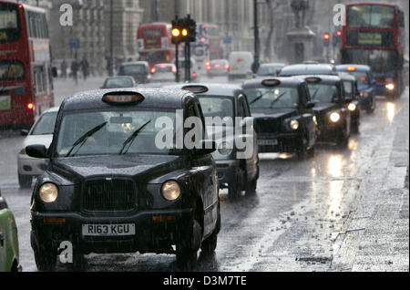 (dpa) (FILE) - The picture shows typical black taxi cabs on a rainy day in London, UK, 07 June 2005. About one week - Stock Photo