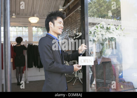 New generation Chinese entrepreneur, putting up 'open' sign at the door of his shop in trendy district of Dong Cheng - Stock Photo