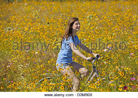 Smiling girl riding bicycle among wildflowers in sunny meadow - Stock Photo