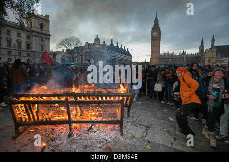 Protesting students dancing round a park bench which has been set on fire in Parliament Square, with the Big Ben - Stock Photo