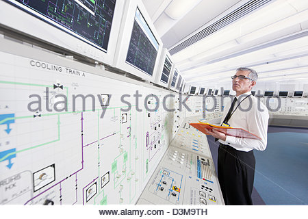 Engineer looking up at monitors in control room of nuclear power station - Stock Photo