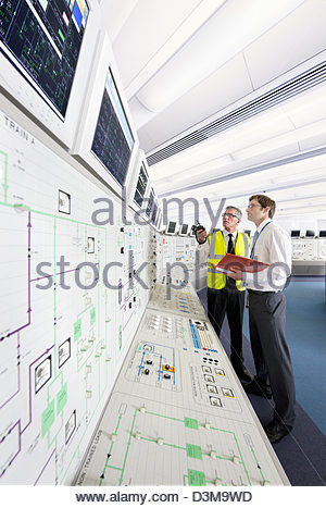 Engineers looking up at monitors in control room of nuclear power station - Stock Photo