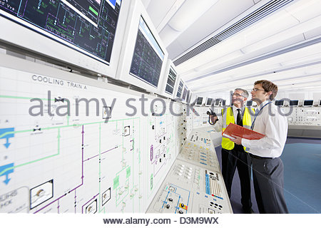 Engineers looking up at computer monitors in control room of nuclear power station - Stock Photo