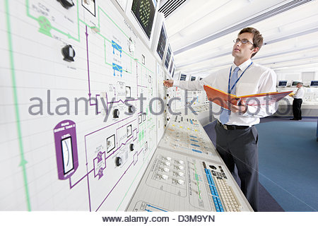 Engineer looking up at computer monitors in control room of nuclear power station - Stock Photo