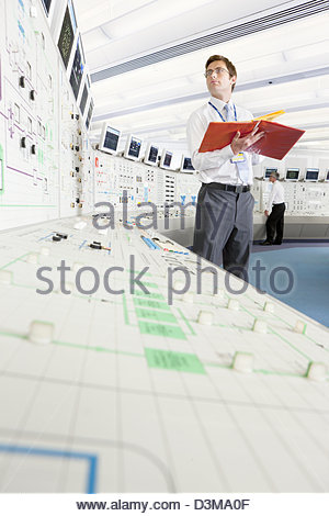 Engineer with binder looking up at computer monitor in control room of nuclear power station - Stock Photo