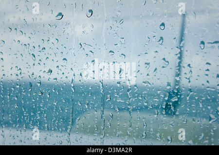 View of raindrops running down the window on a catamaran during monsoon off the northern coast of Mauritius. - Stock Photo