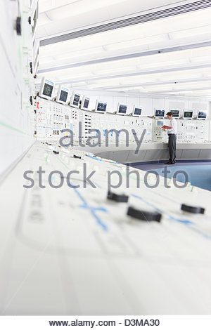 Engineer at control panel in control room of nuclear power station - Stock Photo