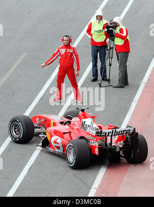 German Formula One pilot Michael Schumacher drives his new '248 F1' race car back to the pits after the first test - Stock Photo