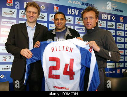 Hamburger SV's new striker Brazilian Ailton (C) presents his new jersey together with head coach Thomas Doll (R) - Stock Photo