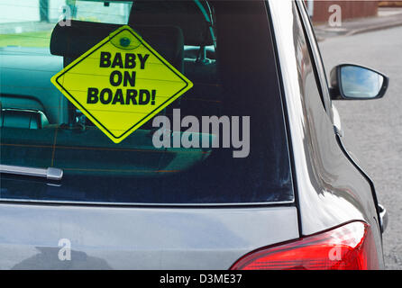 Baby on board warning sign in the back window of a car to advise cars behind of the presence of a toddler - Stock Photo