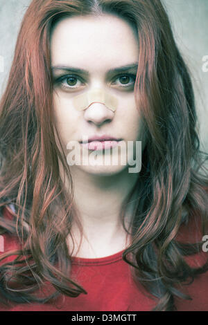 Portrait of a young woman with a band-aid on her nose - Stock Photo