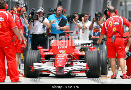 The members of the Ferrari F1 team stand around the racing car of German Formula One driver Michael Schumacher during - Stock Photo