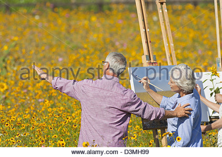 Senior man guiding woman painting in sunny wildflower meadow - Stock Photo