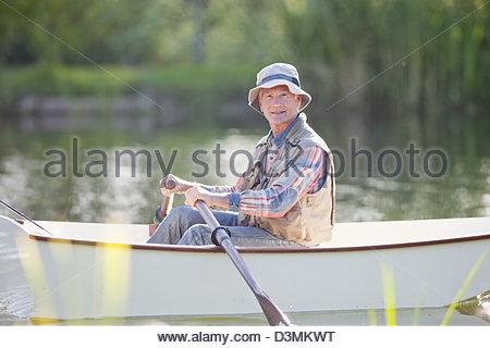 Portrait of smiling senior man fishing in rowboat on sunny lake - Stock Photo