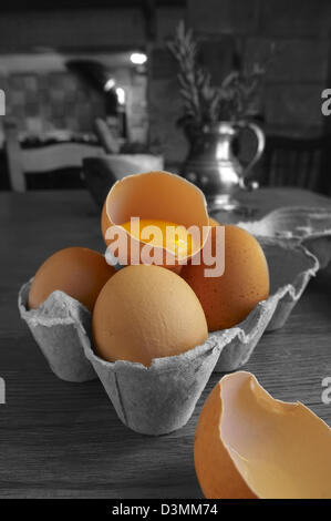 Fresh eggs with one cracked in half - Stock Photo
