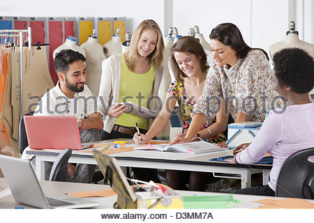 Fashion design students working together in classroom - Stock Photo