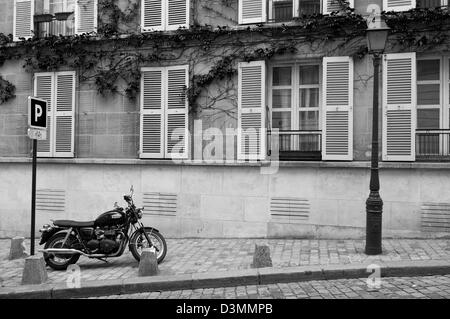 A motorcycle parked on the sidewalk in the quaint Montmartre neighborhood in Paris, France. - Stock Photo