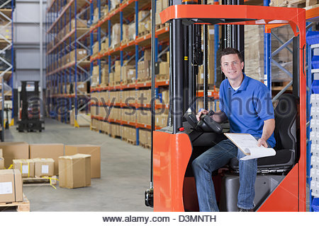 Portrait of smiling worker sitting in forklift with paperwork in distribution warehouse - Stock Photo