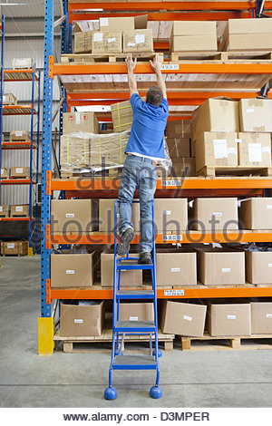Worker on ladder reaching for cardboard box on shelf overhead in distribution warehouse - Stock Photo