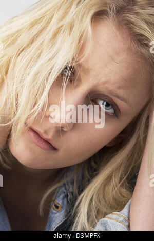 Portrait of a sad young woman with blond tousled hair looking desperate and holding her hand to the head. Studio - Stock Photo