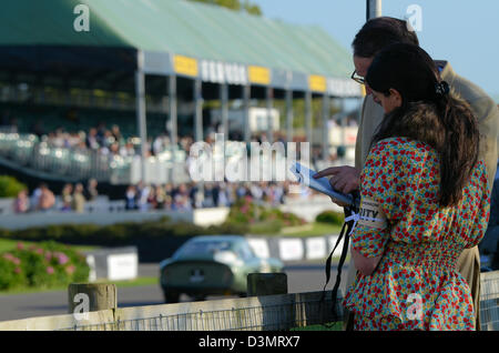 Spectators at the Goodwood Revival discuss the race card as a classic car passes. Period outfits, costumes, attire. - Stock Photo