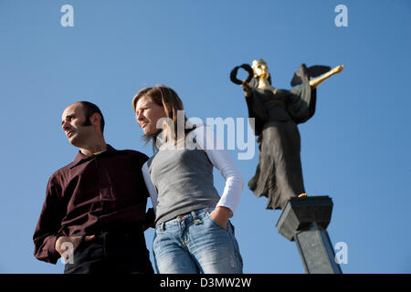 Sofia, Bulgaria, two young men in front of the Statue of Liberty Black Angel - Stock Photo
