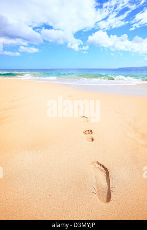 Beach travel vacation concept - footsteps in sand on beautiful sunny day during getaway holidays under the sky, - Stock Photo