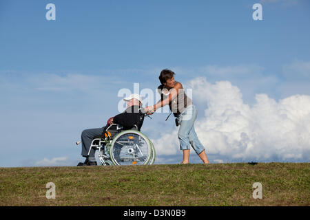 Sankt Margen, Germany, a woman pushing a wheelchair with an older master - Stock Photo