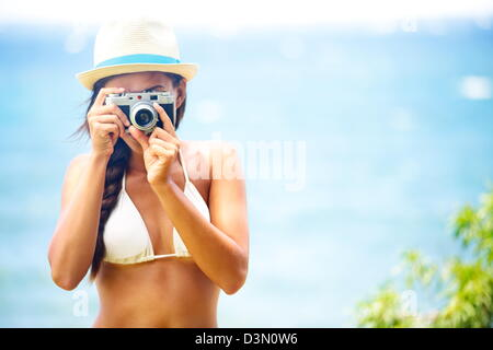 Summer beach woman holding vintage retro camera taking pictures during summer holiday vacation travel at the ocean - Stock Photo