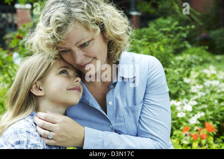 Mother embraces and comforts daughter - Stock Photo