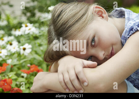 7 year old girl hugging her knees - Stock Photo
