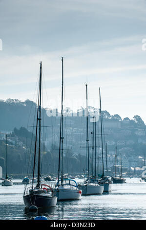 Sailing boats moored in a line on a calm and still River Dart looking towards Kingswear on a grey and blue tonal - Stock Photo