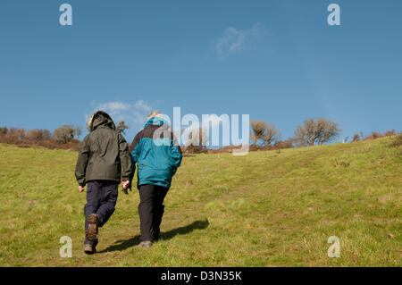 Two ramblers in walking jackets, boots and trousers energetically walking up a steep hill on a sunny spring day - Stock Photo