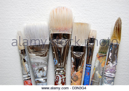Closeup studio shot assorted well used artists large acrylic paint brushes plain background. - Stock Photo