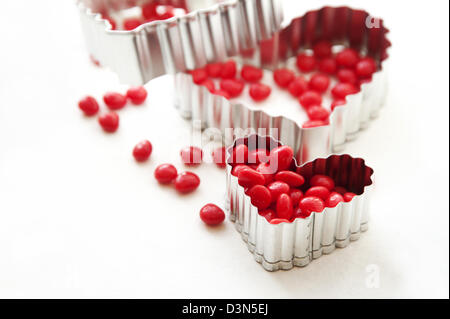 Red candy cinnamon hearts and heart shaped cookie cutters - Stock Photo