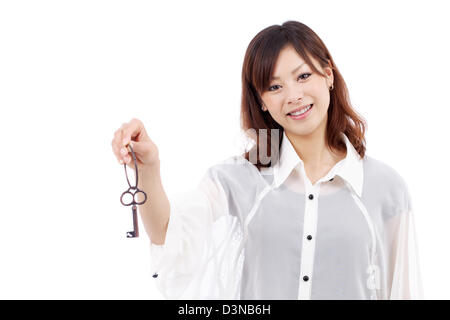 Beautiful young asian woman holding keyring in her hand - Stock Photo